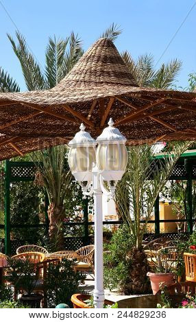 White Lantern And Wicker Umbrella In A Cafe. Design Of Cafe