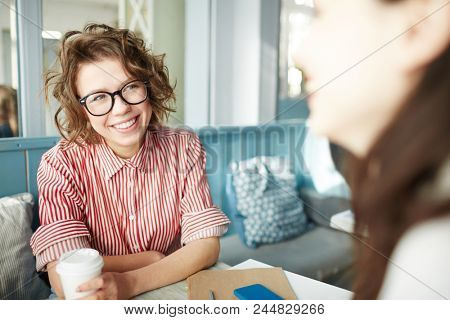 Happy girl in eyeglasses and striped shirt looking at her friend while sitting in cafe, having drink and talking