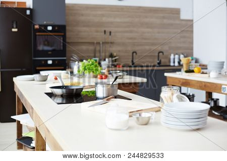 Workplace of chef with pan and frying-pan on electric stove and kitchenware on table