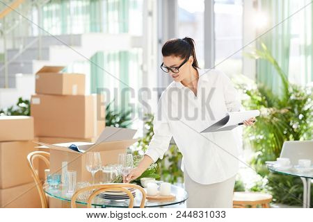 Positive confident female event manager in glasses unpacking box with crockery and decorations while checking it and filling report at workplace