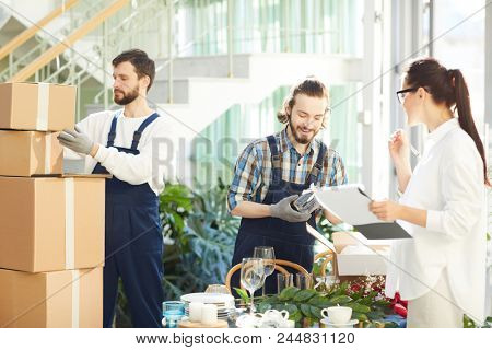 Confident successful event planner using checklist while examining delivery of crockery and decorations while positive movers unpacking boxes