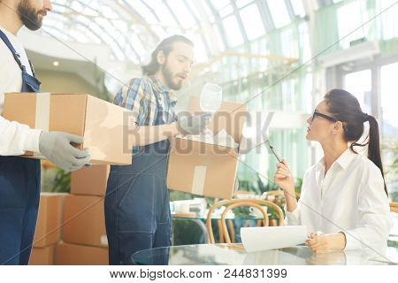 Serious confident female restaurant manager in glasses asking mover about goods and examining wineglasses shown by movers while taking delivery in lobby of new public establishment.