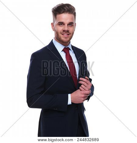 portrait of smiling businessman in navy suit and red tie fixing his sleeves while standing on white background