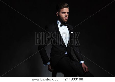 portrait of elegant young man wearing tuxedo sitting on wooden chair while looking to side on black background