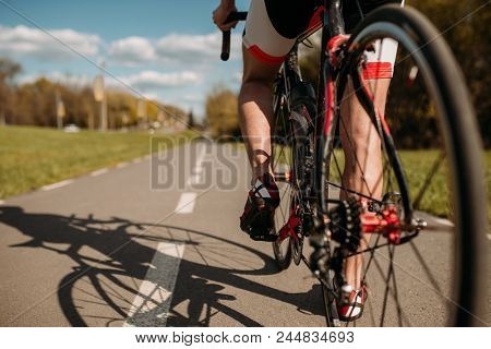 Cyclist on bike path, view from the rear wheel