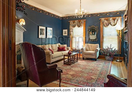 Dayton, Ohio, USA - June 10, 2018: Example of Victorian living room with navy blue walls, ten foot ceiling, crystal chandelier and orential area rug in one hundred-year-old home.