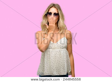 Young woman wearing sunglasses with heart shape covers mouth in shock, looks shy, expressing silence and mistake concepts, scared