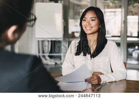 Portrait of joyful asian woman smiling and holding resume while sitting in front of businesswoman during corporate meeting or job interview - business, career and placement concept