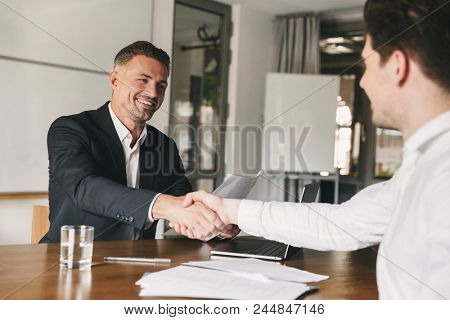 Business, career and placement concept - joyful handsome businessman 30s smiling and shaking hands with male candidate who was recruited during interview in office poster