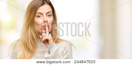 Young beautiful woman with index finger on lips, ask to be quiet. Silence and secret concept