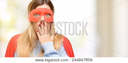 Young super woman covers mouth in shock, looks shy, expressing silence and mistake concepts, scared