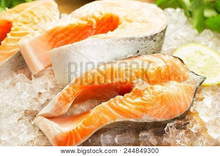 Close-up View Of Salmon Steaks On Ice With Greens And Lemon