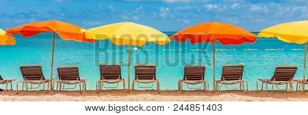 Beach chairs and umbrellas vacation tropical Holiday travel Banner. Caribbean beach on Sint Maarten with retro colorful parasols and loungers, turquoise blue ocean water. Panoramic crop.