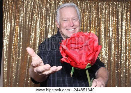A happy middle aged man in a Photo Booth.   A happy man laughs holds a Giant Red Rose as he smiles while in a Photo booth at a Party. Party Time Photo Booth.