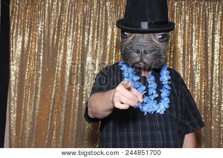A happy middle aged man in a Photo Booth.  A man wears a Dog Mask and Top Hat while posing in a Photo Booth at a party. Party Time Photo Booth.