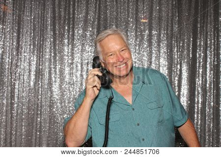 A happy middle aged man in a Photo Booth.  A happy man talks on a Telephone while in a Photo Booth at a Party. Party Time Photo Booth