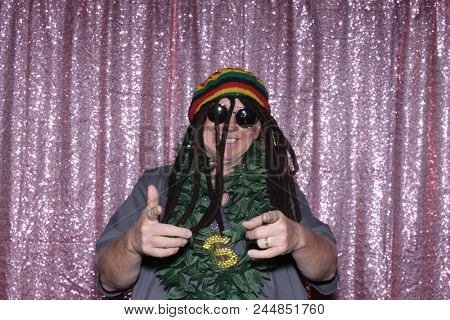 A happy middle aged man in a Photo Booth.   A happy man laughs, points and smiles while wearing a Rastafarian Hat and Marijuana Leaf Lea while in a Photo booth at a Party. Party Time Photo Booth.