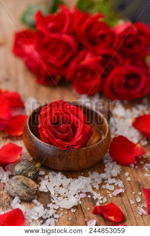 rose in bowl with pile of salt ,stones with rolled towel on old wooden board