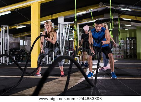 young fit sports couple working out in functional training gym doing  battle ropes cross fitness exercise