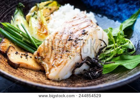 Modern Japanese fried cod fish filet with bok choi and rice as top view in a bowl