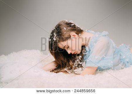 Tenderness And Fragility Of Youth Concept. Side View Teenage Girl Lying On Drowsy Bed On Gray Backgr