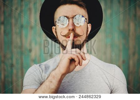 Young Bearded Hipster Man In Sunglasses With Fashionable Mustaches Gesturing For Silence With Finger
