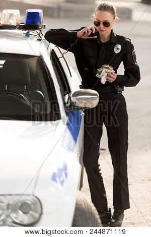 Policewoman In Sunglasses With Burger In Hand Talking On Portable Radio