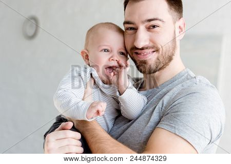 Young Smiling Father Holding Little Baby Boy At Home