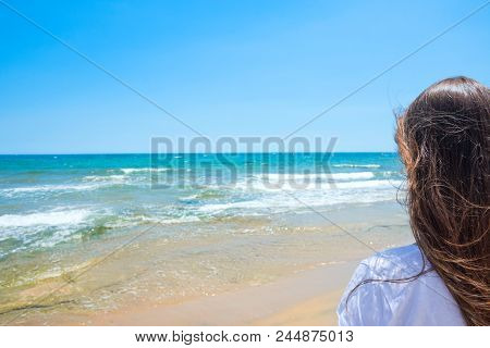 Young Attractive Caucasian Woman With Long Chestnut Hair With Back To Viewer Stands On Sand Beach Lo