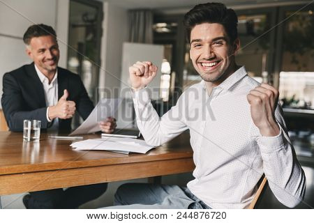 Career, office and placement concept - successful caucasian man 30s rejoicing and clenching fists during job interview with employee of big company