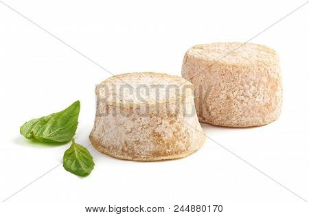 Two Crottin Cheese With Basil Leaves Isolated On White Background