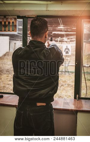 Man Firing With Pistol On Target At The Shooting Range. Close-up.