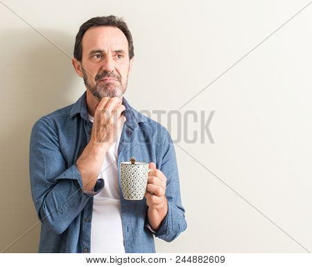 Senior man drinking coffee in a mug serious face thinking about question, very confused idea