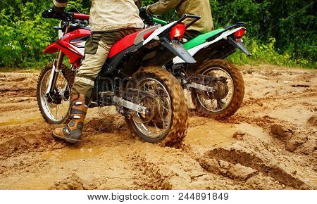 Motocross Racers Racing On The Off-road Circuit Mud Flying Through Air. Motorbike Rides Through The