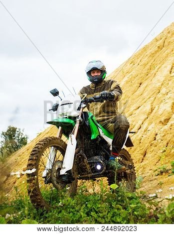 Man Wearing Motorcycle Helmet And Safety Uniform Sitting On A Dirt Bike Outdoors, Beautiful Scenic L