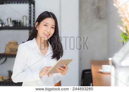 Beautiful Portrait Young Asian Woman Using Tablet Computer In The Coffee Shop, Businesswoman Sitting