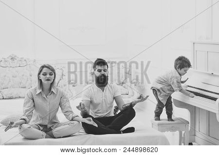 Mom And Dad Try To Keep Calm. Meditation Concept. Young Parents Meditating, While Their Little Son P