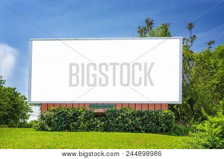 Horizontal Shot Of A Blank Neighorhood Billboard Under A Blue Sky Surrounded By Greenery.
