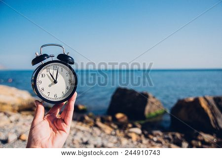 Hand Hold Watch On Beach Background.alarm Clock On Sea And Sand Background Different Time With Summe