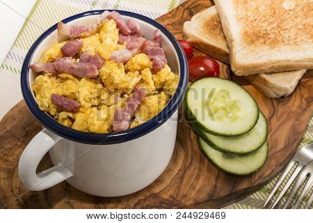 Scrambled Eggs With Roasted Bacon In An Enamel Mug, Served With Toasted Slice Of Bread, Cucumber Sli
