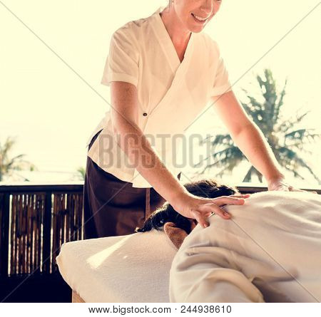 Female massage therapist giving a massage at a spa