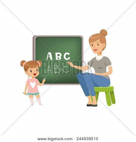 Cute Little Girl Standing Near The Blackboard And Writing Letters Of The English Alphabet, Teacher H