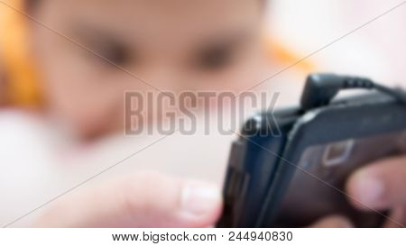 Blurred People - A Boy Still On The Bed Playing With His Mobile Phone. Relax Background Concept.