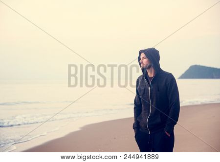 Man walking in solitude at the beach poster