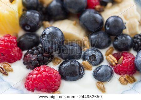 Plate of mixed fruits with yogurt, raspberry, blueberry, banana, gooseberry