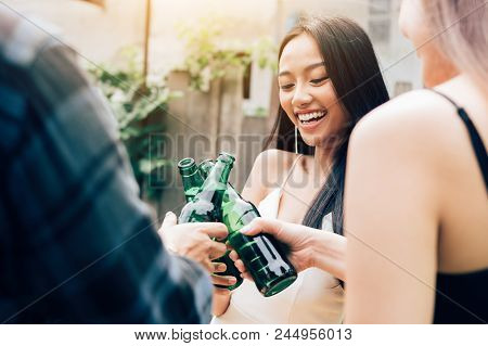 Asian Group Enjoying Toasting Drinks Party With Clinking Beer Bottle.