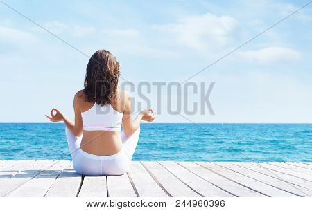 Woman In White Sporty Clothes Meditating On A Wooden Pier On Summer.  Sea And Sky Background. Yoga,