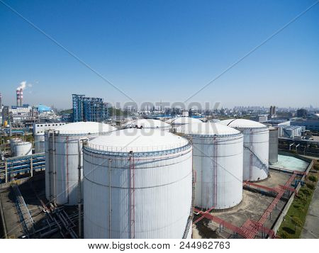 Oil storage tank with oil refinery background