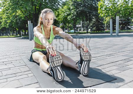Fit fitness woman doing stretching exercises outdoors at park. Girl doing hamstring leg stretching exercise and stretches. Female sports model exercising outdoor in summer. poster