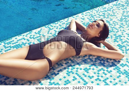 Young brunette woman in swimsuit. Girl relaxing and getting tan in swimming pool. Summer, traveling, resort and vacation concept.